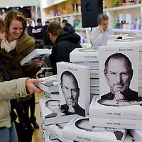 Customer takes a piece from the stack of books during the premiere of the Steve Jobs biography written by Walter Isaacson published in Hungarian translation in Budapest, Hungary on November 28, 2011. ATTILA VOLGYI
