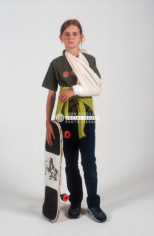 Portrait of young girl with broken arm in sling holding skateboard,