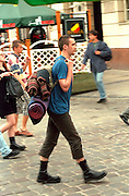 Man age 20 walking with backpack and blanket.  Poznan Poland