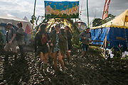 Party people making their way through mud at Glastonbury Festival 25th July 2016, Somerset, United Kingdom.  The Glastonbury Festival runs over 3 days and has 3000 acts, including music, art and performance and approx. 150.000 attend the anual event.