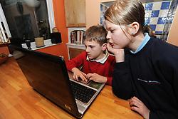 Children on laptop computer in kitchen MR