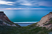 A dusk view looking down Sheringham's steep cliffs to a shingle beach and The North Sea beyond. North Norfolk, East Anglia.