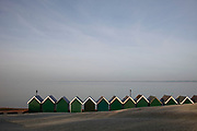 A line of traditional green beach huts on frozen ground in winter look out to sea across the Solent at Gurnard on the Isle of Wight.