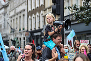 A young girl holds a megaphone while members of the Extinction Rebellion set up a camp at the busy junction on St Martin's Lane near Covent Garden in central London on Monday, Aug 23, 2021. (VX Photo/ Vudi Xhymshiti)