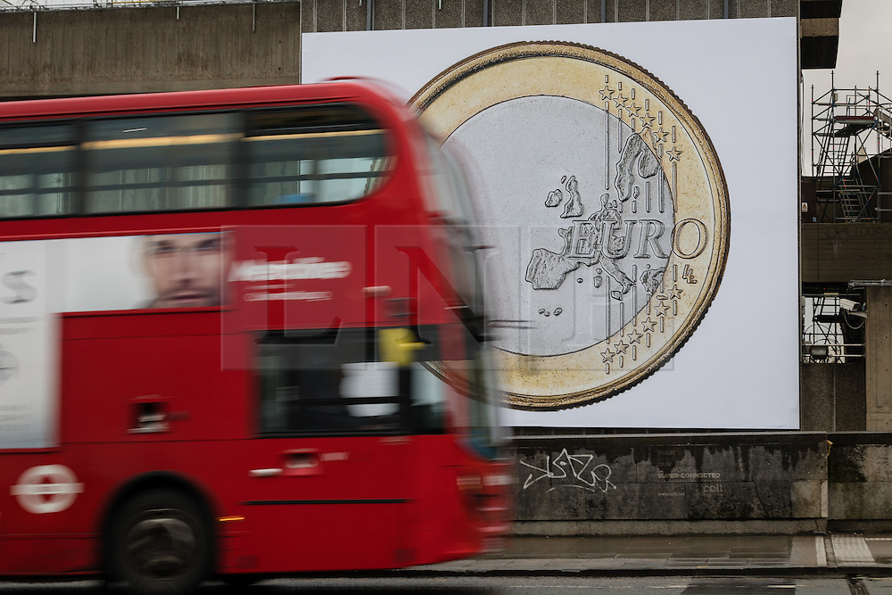 © Licensed to London News Pictures. 02/02/2017. LONDON, UK.  A red double decker bus passes the artwork 'Euro (2012)', by Danish artists Superflex, as it hangs on the wall of the South Bank Centre. The artwork will be on display in London until the end of February. MP's last night voted in Parliament to back the 'Brexit Bill' and trigger Article 50, to begin the formal Brexit process for the United Kingdom leaving the European Union.  Photo credit: Vickie Flores/LNP
