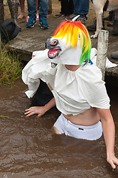 © Licensed to London News Pictures. 30/08/2015. Llanwrtyd Wells, Powys, Wales, UK. Arry Beresford-Webb (front) from cardiff & Eva Walters from Wrexham dress as a unicorn for the bog event. World Bogsnorkelling Championships, conceived 30 years ago in a Welsh pub by landlord Gordon Green, are held every August Bank Holiday at Waen Rhydd Bog. Using unconventional swimming strokes, participants swim two lengths of a 55 metre trench cut through a peat bog wearing snorkel and flippers. The world record was broken in 2014 by 33 year old Kirsty Johnson from Lightwater, Surrey, in a time of 1 min 22.56 secs. Photo credit: Graham M. Lawrence/LNP