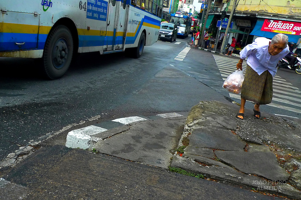 Woman slowly crossing the street in Bangkok