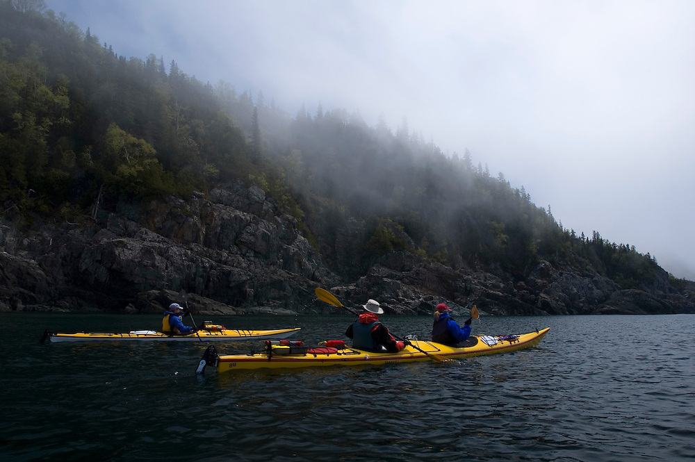 Sea kayakers paddle through lifting fog in Lake Superior Provincial Park near Wawa Ontario Canada.