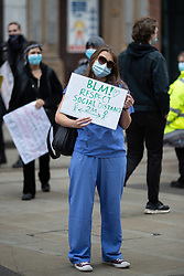 © Licensed to London News Pictures. 07/06/2020. Manchester, UK. A woman wearing medical scrubs stands at the periphery of the demonstration carrying a sign urging people to respect social distancing of 2 metres . A Black Lives Matter demonstration against police violence is held in Manchester City Centre . Ongoing protests have and are being held in Manchester and around the world , after George Floyd was killed whilst being restrained by police in Minneapolis on 25th May 2020 . Photo credit: Joel Goodman/LNP