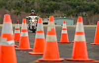 Laconia Patrolman Robb Sedgley works his way through a series of cones during the Police Motorcycle Driving Course at Laconia Airport on Wednesday morning.  (Karen Bobotas/for the Laconia Daily Sun)
