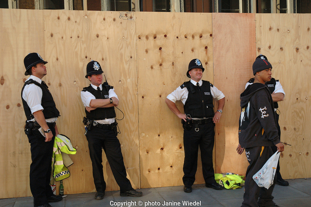 Four police officers on beat standing against wall in West London during Notting Hill Carnival.