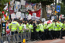 """Cricklewood, London, July 19th 2014. Large numbers of police keep scores of counter-protesters separate from a protest by about 13 far-right anti-Islamists from the """"South East Alliance"""" as they demonstrate outside the London offices of Egypt's Muslim Brotherhood."""