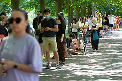 © Licensed to London News Pictures 18/07/2021. Greenwich, UK. People queueing in the heatwave sun to get a vaccination. Hundred of people turn up at a Pfizer covid vaccination event for over 18s in Greenwich Park, London today between noon and 7pm. Photo credit:Grant Falvey/LNP