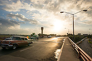 At sunset, a vintage car working as a taxi and carrying foreign tourists approaches the drop-off curb at Jose Marti International airport in Havana, Cuba. An airport control tower and people are in the background. Car exhaust is visible behind the car.