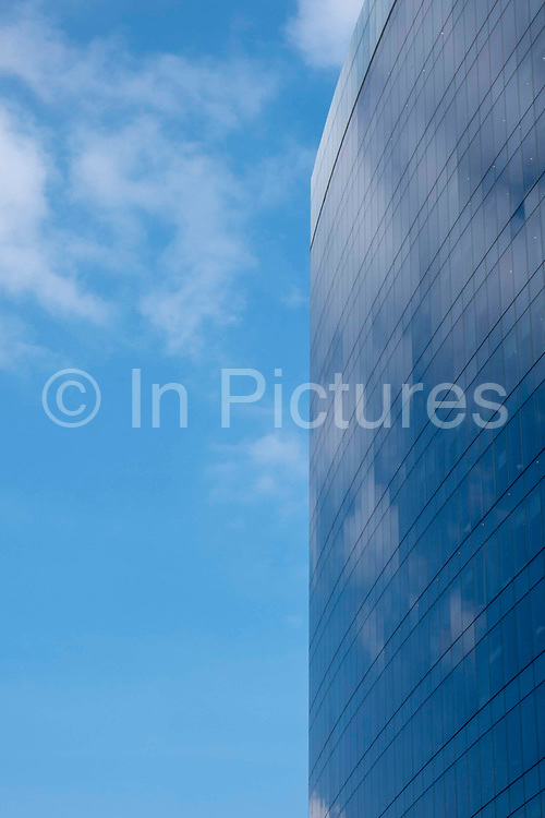 A glass building in Whitechapel reflecting the beautiful blue sky, mirroring nature, Whitechapel, London, United Kingdom.