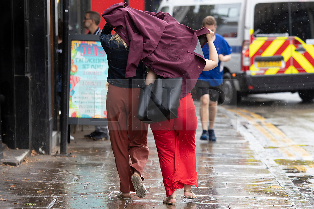 © Licensed to London News Pictures. 27/07/2021. London, UK. Member son the public hold a jacket above their heads to shelter from rain in Greenwich, South East London. A yellow weather warning for thunderstorms is in place for parts of England. Photo credit: George Cracknell Wright/LNP