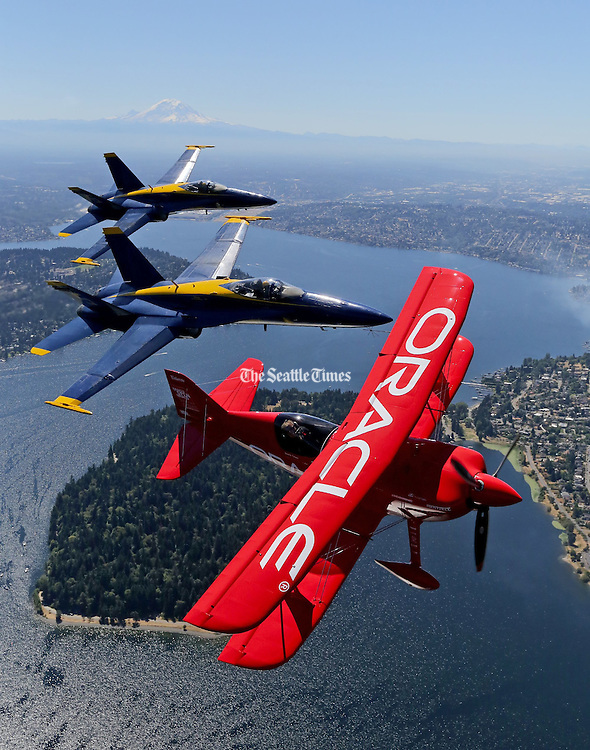 Aerobatic pilot Sean Tucker with his Team Oracle plane, flies in formation over Seattle. Blue Angel pilots LCDR Mark Tedro in #5 and Lt Ryan Chambertlain in #6. (Greg Gilbert / The Seattle Times, 2015)