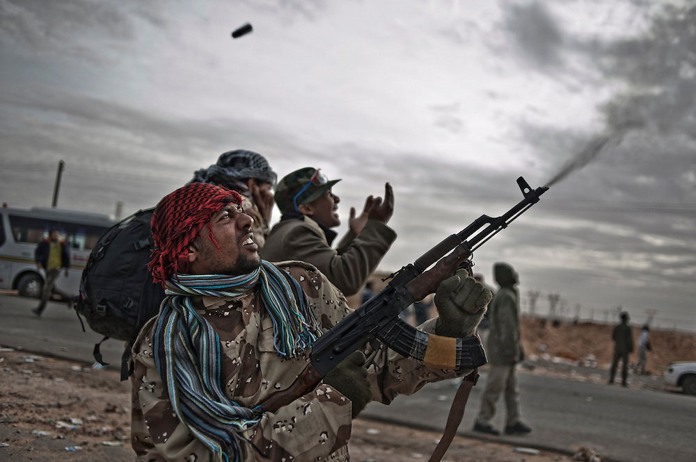 A rebel is shooting with his kalachnikov while a other one is praying during an air strike of Kadhafi forces. Ras Lanuf, Libya - March 10th 2011.