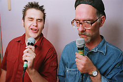 Support worker for people with learning disabilities with man with learning disability singing karaoke into microphones in community centre,