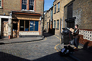 Busker plays his guitar on a famous but deserted corner at Columbia Road flower market on Mothers Day, and its last open Sunday for a while due to Covid-19 on what would normally be a busy, bustling market day with hoards of people out to buy flowers and socialise, the numbers of people out is a fraction of a regular Sunday on 22nd March 2020 in London, England, United Kingdom. All of the East End Sunday markets have been affected by the Coronavirus outbreak, with some completely closed and some currently partially open. Coronavirus or Covid-19 is a new respiratory illness that has not previously been seen in humans. While much or Europe has been placed into lockdown, the UK government has announced more stringent rules as part of their long term strategy, and in particular social distancing.