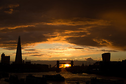 © Licensed to London News Pictures. 12/08/2014. London, UK. Black clouds and an orange sunset are seen behind Tower Bridge and the City of London skyline during  a heavy rain shower and sunset this evening. Photo credit : Vickie Flores/LNP