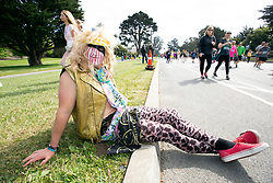 A man costumed as a 1980s rock star waits for the rest of his band to arrive at the 107th running of the Bay to Breakers, Sunday, May 20, 2018, in San Francisco. (Photo by D. Ross Cameron)