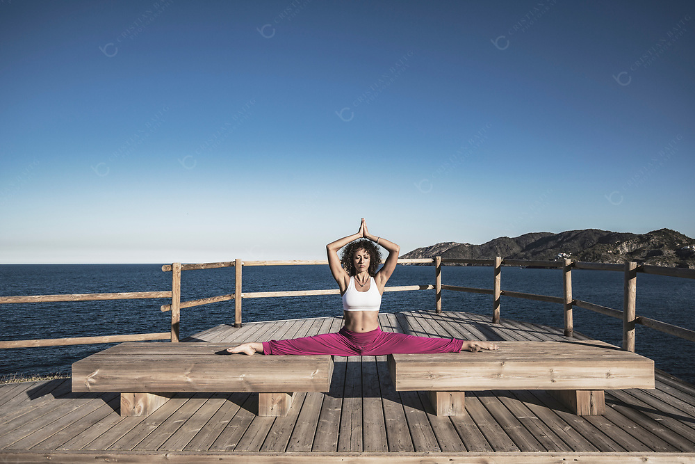 Young woman exercising and doing split outdoors at the sea