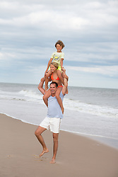 man with two kids on his shoulders at the beach in East Hampton, NY