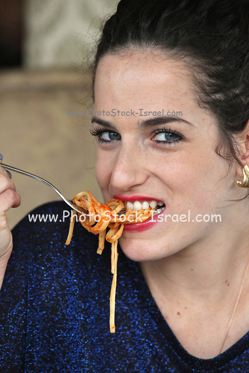 Young woman eats spaghetti with tomato sauce