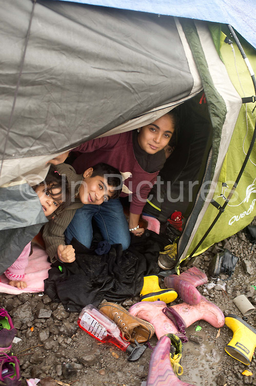 France. Refugees. Grande Synthe camp near Dunkirk. People are camping in a wood with very few facilities.  Three children from a Kurdish family from Iraq shelter in their tent from the pouring rain.