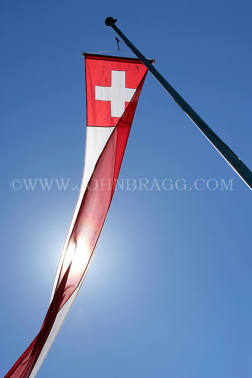 The flag of Switzerland in a long narrow red and white pennant style.