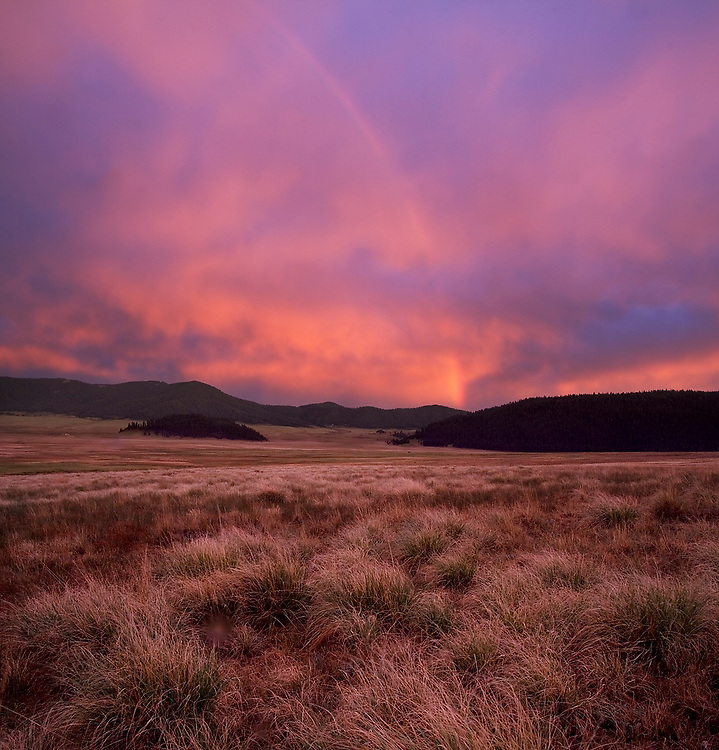 A crimson sunset and rainbow drown in warm light the Valle Grande, Valles Caldera National Preserve, New Mexico on June 26, 2006.