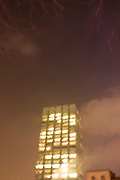 Blurred London city lights and office tower at night.