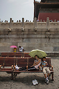 A lady takes a rest inside the Forbidden City.