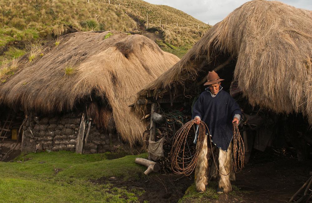 Ecuadorian Chagra (Cowboy) Manuel Changoluisa at his home which is a traditional Chagra sod hut<br /> Paramo (High Andean Grasslands)<br /> Base of Cotopaxi Volcano, Andes<br /> ECUADOR.  South America