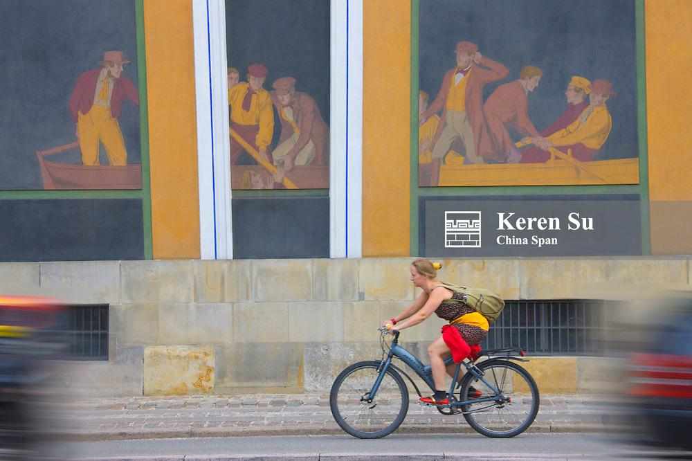 Biker passes by mural on the street, Copenhagen, Denmark