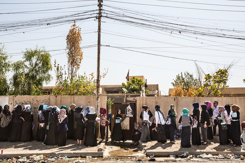 Girls are seen in front of their school after they finish exams after Mosul is liberated. Even though some schools resume classes, they are still afraid of ISIS.