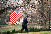 """06 DECEMBER 2020 - DES MOINES, IOWA: A supporter of President Donald Trump carries an American flag during a Trump motorcade at the Iowa State Capitol. About 1,000 supporters of outgoing US President Donald Trump rallied in Des Moines Sunday to show their support for the President and to protest the outcome of the US Presidential election. They started with a rally in the suburbs of Des Moines then drove in a motorcade through the city, ending at the State Capitol. They repeated many of Trump's discredited claims that the election was marked by fraud and that Trump actually won. The protest was a part of the national """"March for Trump"""" effort, culminating in a march in Washington DC on December 13. Joe Biden won the election, with 306 electoral votes to Trump's 232.       PHOTO BY JACK KURTZ"""