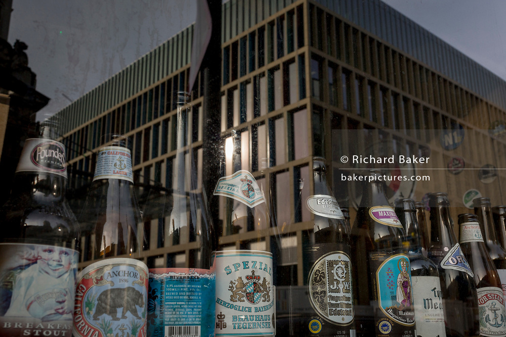 A window display of beer bottles and new architecture of an office workplace, on 20th November 2019, at Smithfield in the City of London, England.