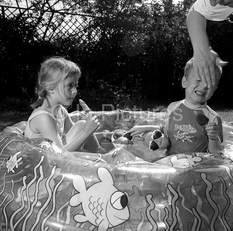 Sitting in cool water of a paddling pool, a 7 year-old girl enjoys an ice lolly while her younger brother winces as he has suncream wiped across his face. They're both enjoying a summer heatwave and the family pool has been inflated and filled with cold water, heated up by the south London sunshine. As the big sister looks on holding her ice cream, the boy reacts at having the sunscreen applied to his skin.