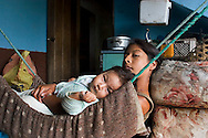 Evelyn Vargas sits with her younger brother Robert in a make shift hammock in their house in Santa Marianitas, Ecuador.