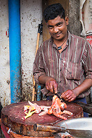 YANGON, MYANMAR - CIRCA DECEMBER 2013: Merchant in the streets of Yangon selling chicken.