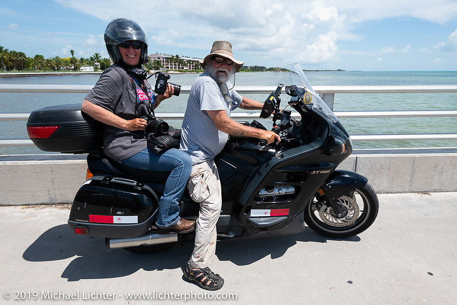 Felicia Morgan took the passenger seat on Joe Sparrow's bike to shoot the Cross Country Chase motorcycle endurance run from Sault Sainte Marie, MI to Key West, FL. (for vintage bikes from 1930-1948). The staging area on a Key West pier just before the finish and near the end of the 110 mile Stage-10 ride from Miami to Key West, FL USA. Sunday, September 15, 2019. Photography ©2019 Michael Lichter.