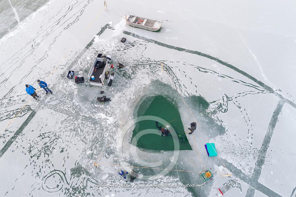 Luftaufnahme vom Weissensee mit Loch zum Eistauchen, Kaenten, Oesterreich / Aerial View from frozen Lake Weissensee with hole for Ice diving in winter, Carinthia, Austria