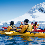 A group of kayakers take a short break to rest on the water at Cuverville Island on the Antarctic Peninsula.