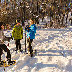Three women take a break while snowshoeing in the forest on Indian Hill in West Newbury, Massachusetts.