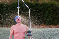 © Licensed to London News Pictures. 03/01/2017. London, UK. A man takes a shower after swimming in The Serpentine Lake in Hyde Park, London on a frosty morning as temperatures in the capital drop below zero celsius on Tuesday, 3 January 2017. Photo credit: Tolga Akmen/LNP