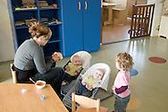 """Nederland, Herpen, 20090128...De baby's krijgen eten. Kindje kijkt toe...Kinderopvang 'Op de boerderij' in Herpen...""""OP DE BOERDERIJ"""" kinderopvang..is gevestigd bij een vleesveebedrijf te Herpen...Wandelen op het erf van de boerderij....Netherlands, Herpen, 20090128. ..The children take a walk..Childcare on the farm in Herpen. ..""""ON THE FARM"""" childcare ..is located at a beef farm in Herpen.    .."""