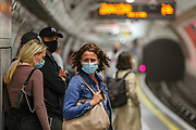 People some of them wearing face protective masks awaits for Bakerloo Line in Oxford Circus underground station in central London on Thursday, Aug 5, 2021. Met Office forecasts 26 hours of heavy rain and thunderstorms to batter the British capital. Severe thunderstorms caused flash flooding across London last Sunday afternoon, sparking major transport delays. (VX Photo/ Vudi Xhymshiti)