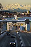 The snow-capped Olympic Mountains loom behind the 520 Bridge over Lake Washington. <br /> <br /> Mike Siegel / The Seattle Times